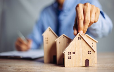 businessman holding small wooden house model